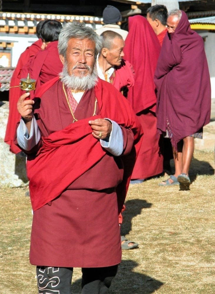 A bearded and red robed monk carries a prayer wheel in Bhutan