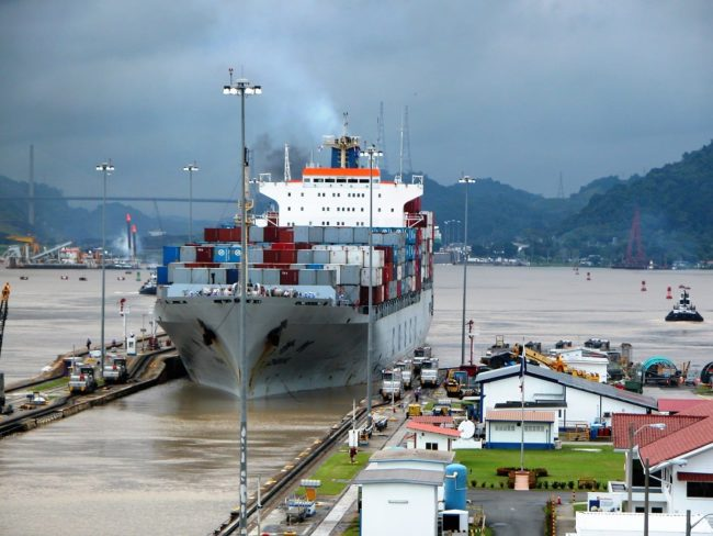 A container ship moving slowly through the locks of the Panama Canal