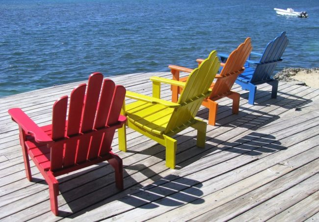 Four painted chairs on the jetty at Roatan, Honduras