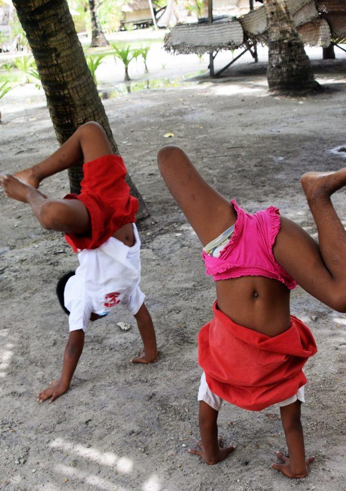 Two schoolchildren doing handstands in their playground