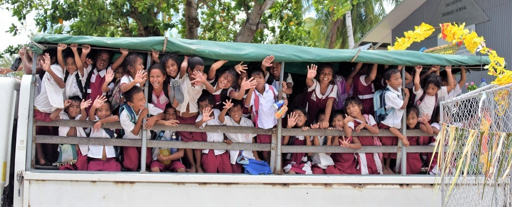 Schoolchildren waving from the open sided lorry taking them to school