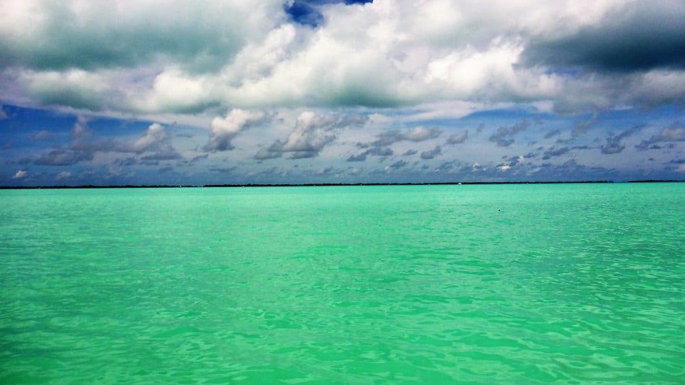 Clouds scud across a green lagoon in Kiribati