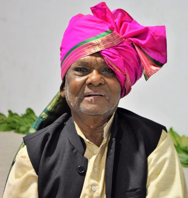 A portrait of a male Indian musician in a pink turban