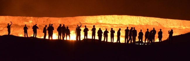 Silhouettes of visitors against the Darvaza crater lit up at night , Turkmenistan