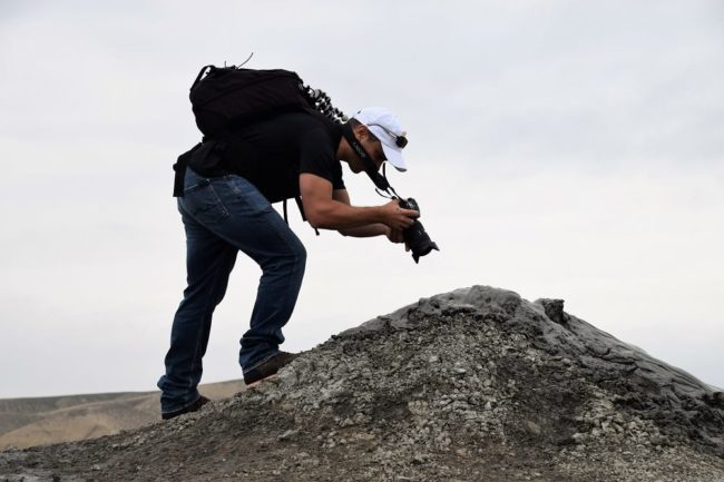 Dr Tino bends over to photograph a mud volcano in Azerbaijan
