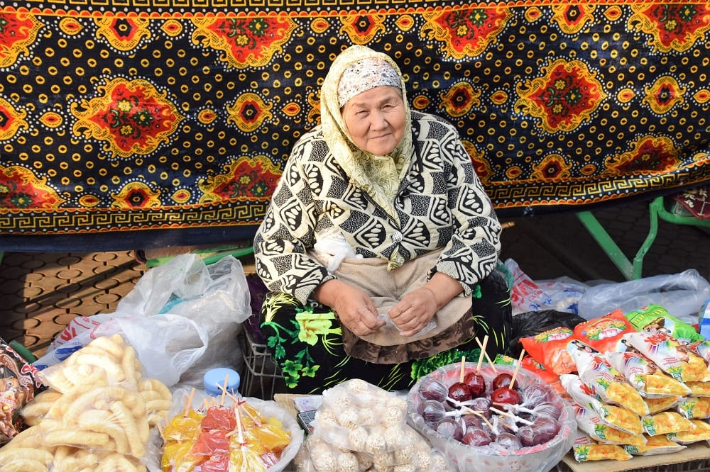A seated lady selling food at the bazaar in Khujand Tajikistan