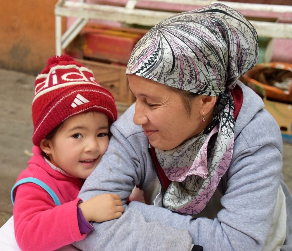 A portrait of a headscarfed lady with her daughter at the bazaar in Khujand Tajikistan