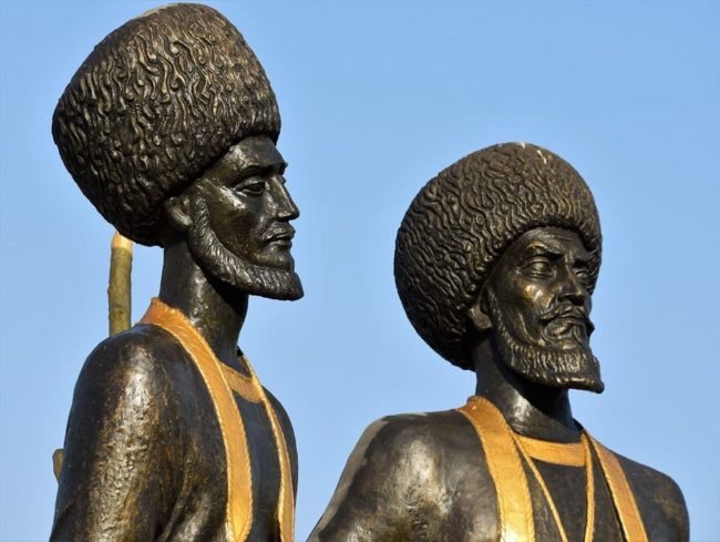 A close up of the heads of black statues of Turkmen warriors
