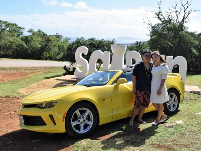 Tourists with a yellow Mustang posing in front of a Saipan sign