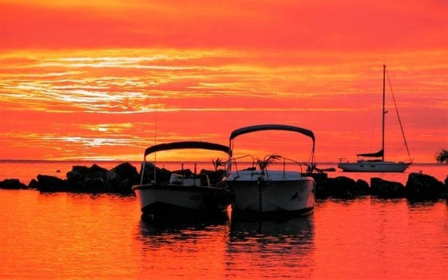 Sunset turns the sea and sky bright orange around boats in Canoe Bay