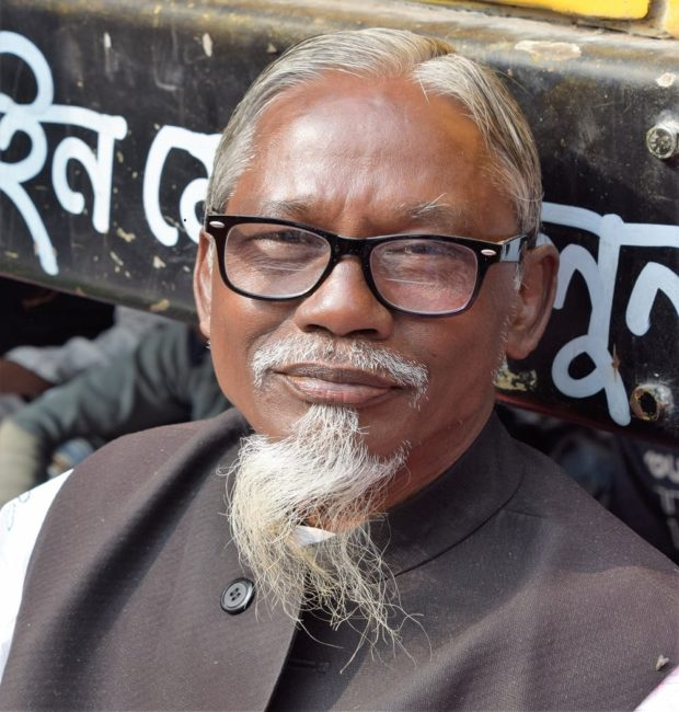 A bespectacled white haired Bangladeshi man with a long goatee beard