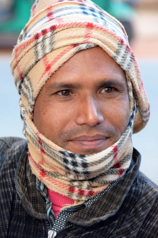Portrait of a young Bangladeshi man swathed in a Burberry patterned scarf