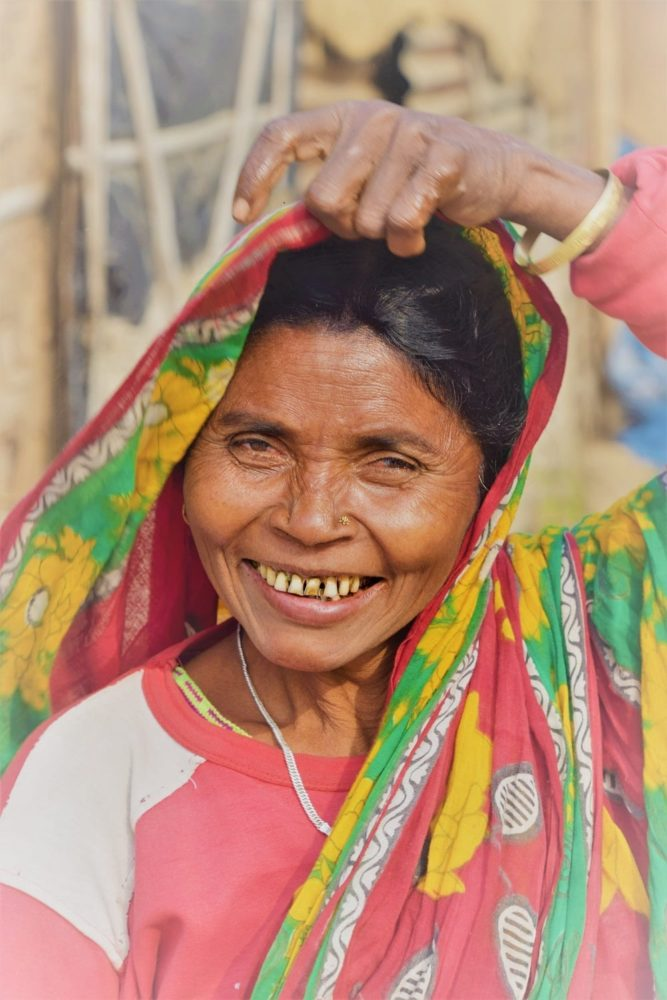 Portrait of a smiling Bangladeshi lady lifting her gaily patterned headscarf