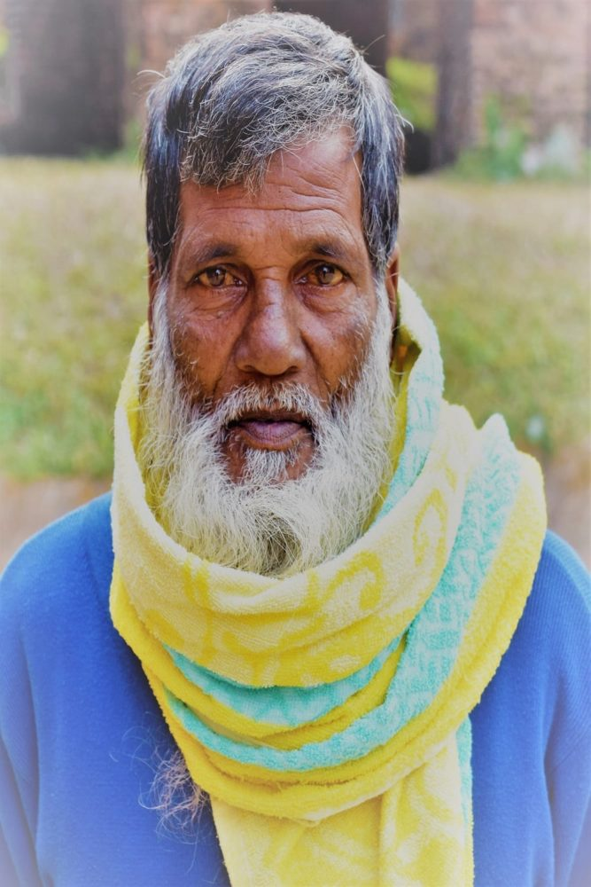 Portrait of a Bangladeshi man with a very long white beard, yellow striped scarf wrapped round his neck