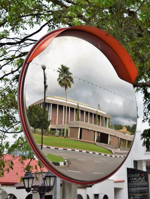 A building reflected in a roadside mirror in Brunei