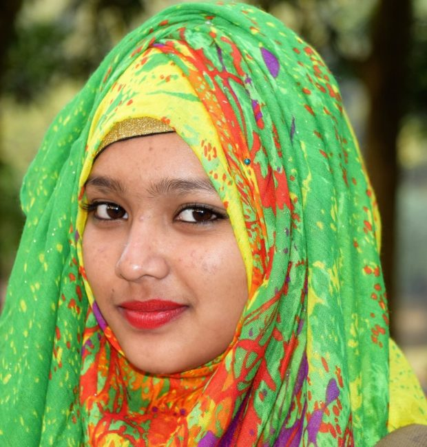 Portrait of a smiling Bangladeshi lady wearing a vibrant green patterned headscarf