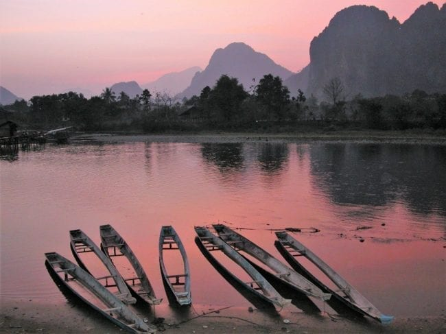 Sunset over the river, canoes and karst scenery at Vang Vieng