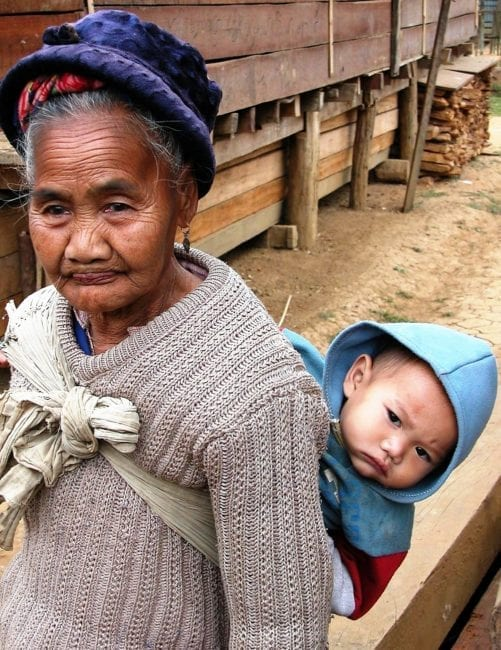 Laos woman carries a baby on her back