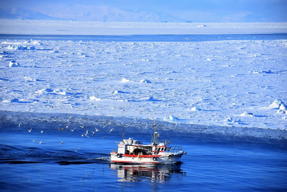 A fishing boat reflected in ultramarine water on the Icefjord, Greenland