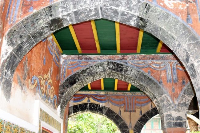 Stone arches and striped painted roof in museum at Constantine