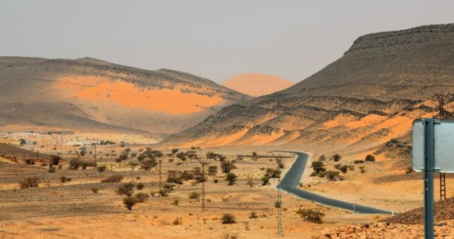 A Sahara desert road cuts through flat topped black mesas scattered with red sand