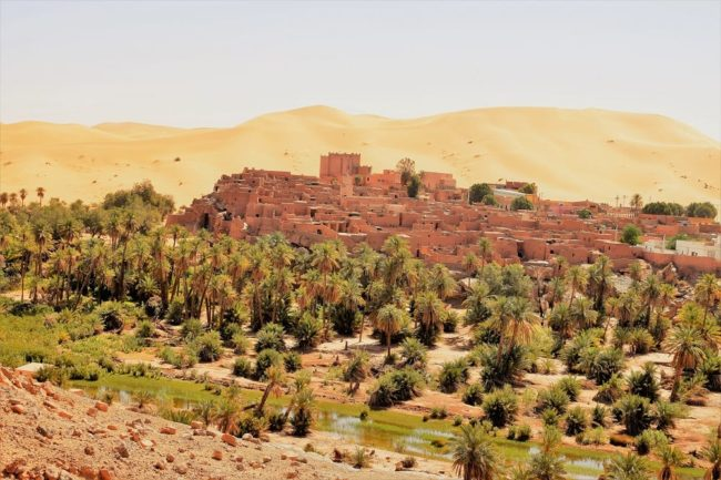 Taghit mudbrick fortress, casbah and oasis spilling picturesquely down the hill in front of a 120 metre high sand dune, Algerian Sahara