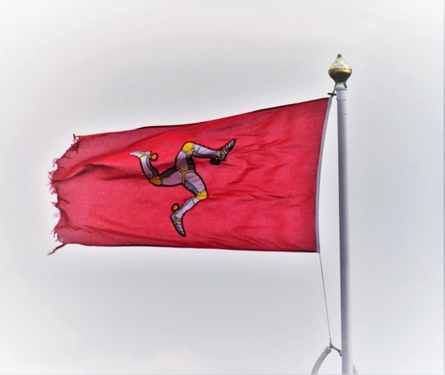 The triskelion - three legs on a red background, the flag of the Isle of Man