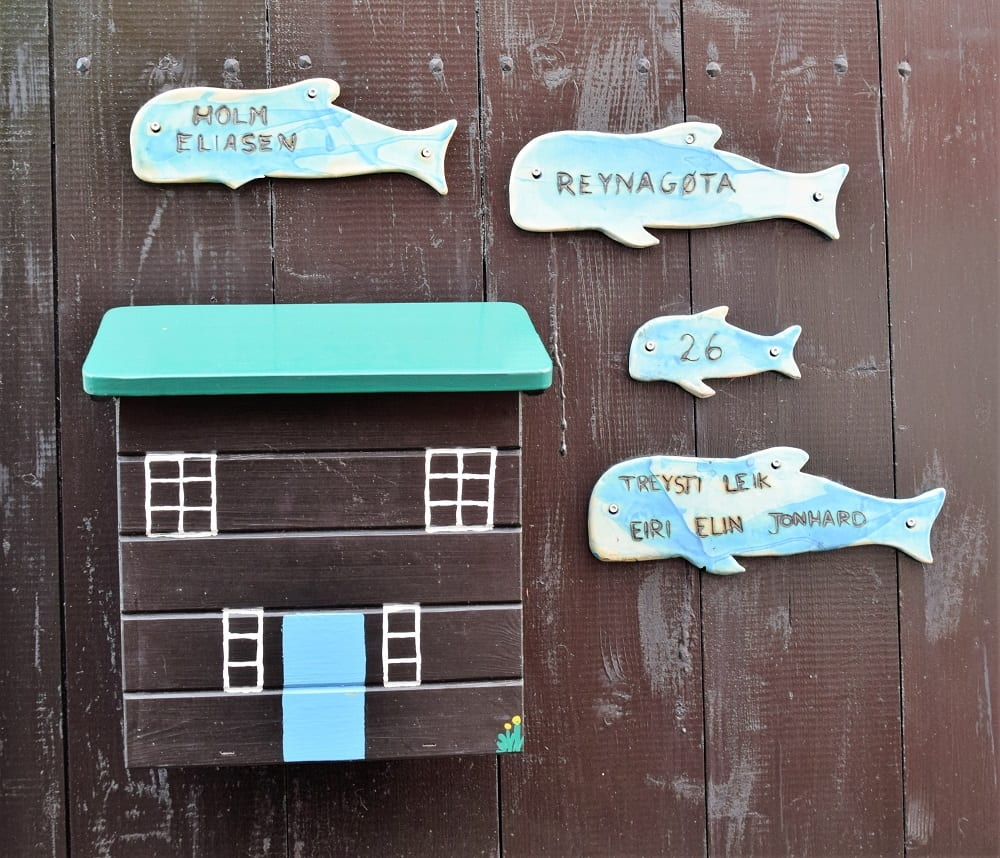 Fish signs and a letterbox on a wooden door in Torshavn