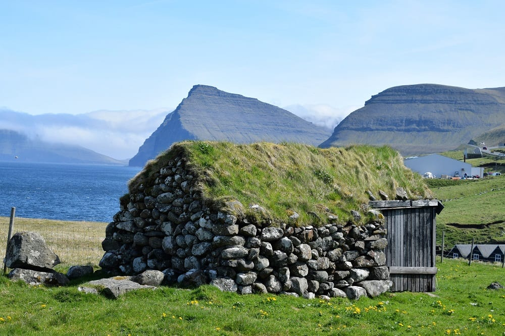 A green turf roofed stone shack in front of jutting peaks, Faroe Islands