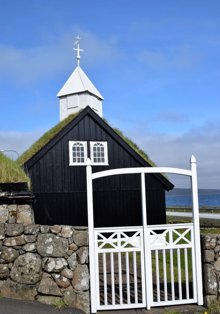 A black and white wood church with pyramid spire and a white angled gate , Faroe Islands