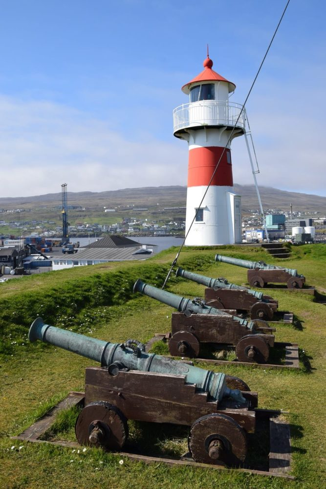 A row of cannons beside the red and white lighthouse at Torshavn