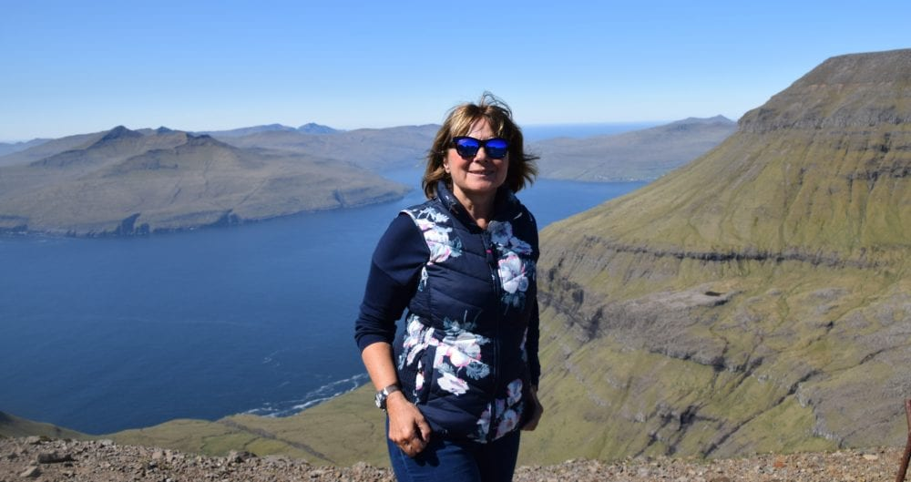 Sue on top of a bright blue fjord lined by mossy green slopes, Faroe Islands