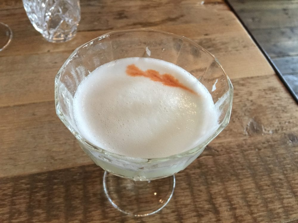 Pisco sour cocktail with foam and classic bitters decoration