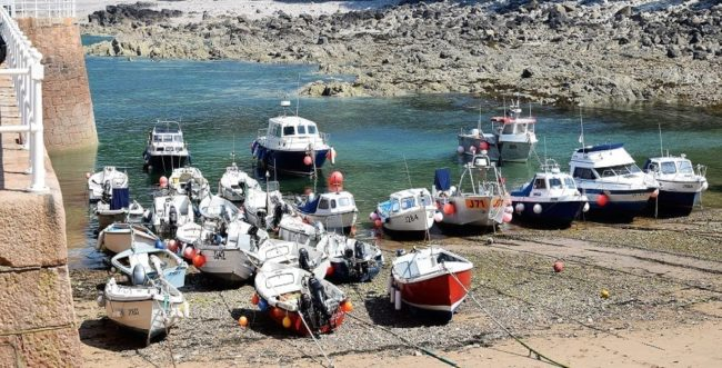 Boats pulled up in the harbour, tide is out, in Jersey