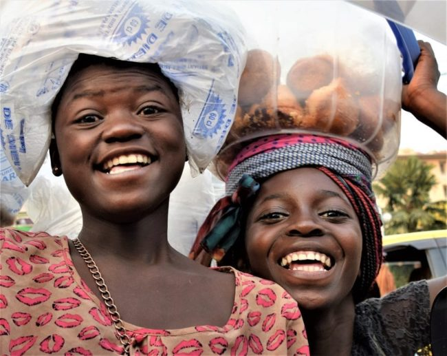 A portrait of two smiling girls selling goods on the roadside DRC