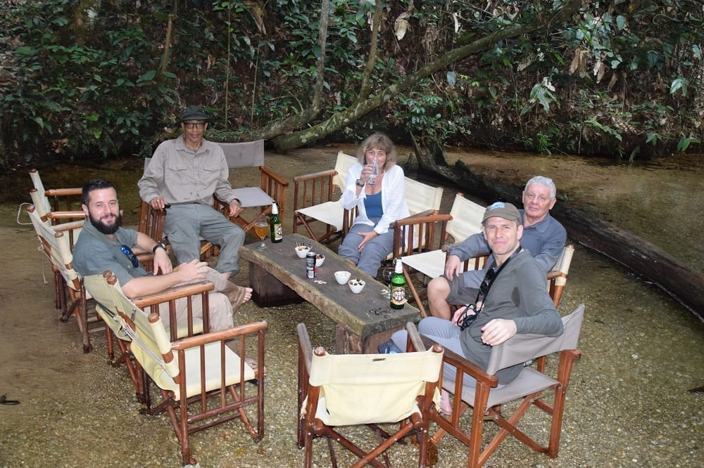 Sue, Clem and guests drinking at a table set in the river, Odzala,
