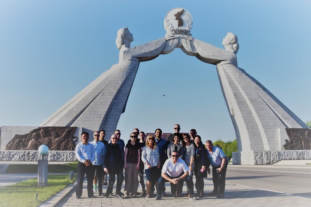 The group pose in front of the National Reunification Arch In Pyongyang