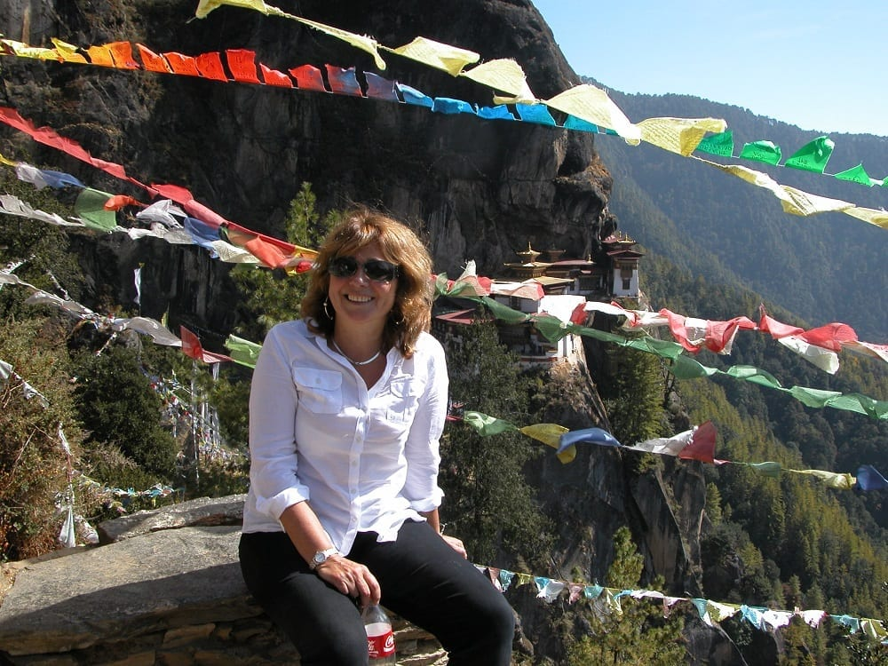 Sue seated in front of waving prayer flags above the Tiger's Nest monastery