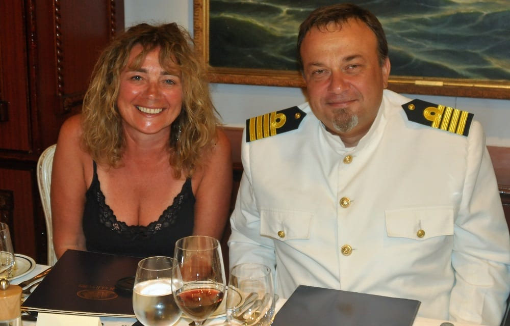 Sue and the captain at dinner on the Star Clipper