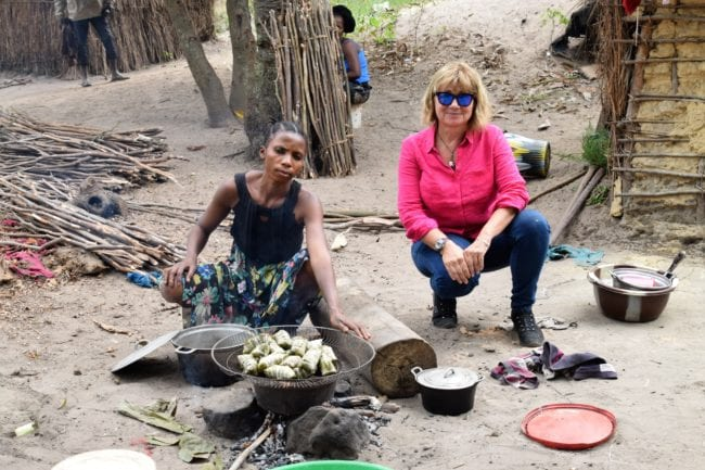 Sue with a villager cooking lunch on an open fire, DRC