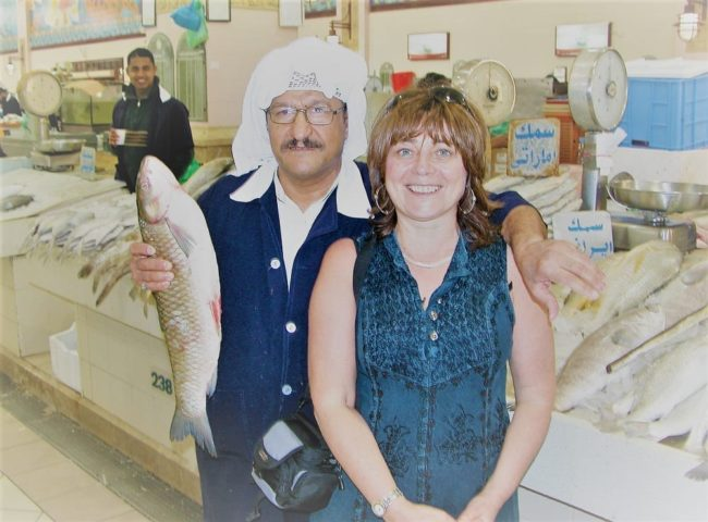 Sue with a Kuwaiti market worker, holding a fish in the fish market