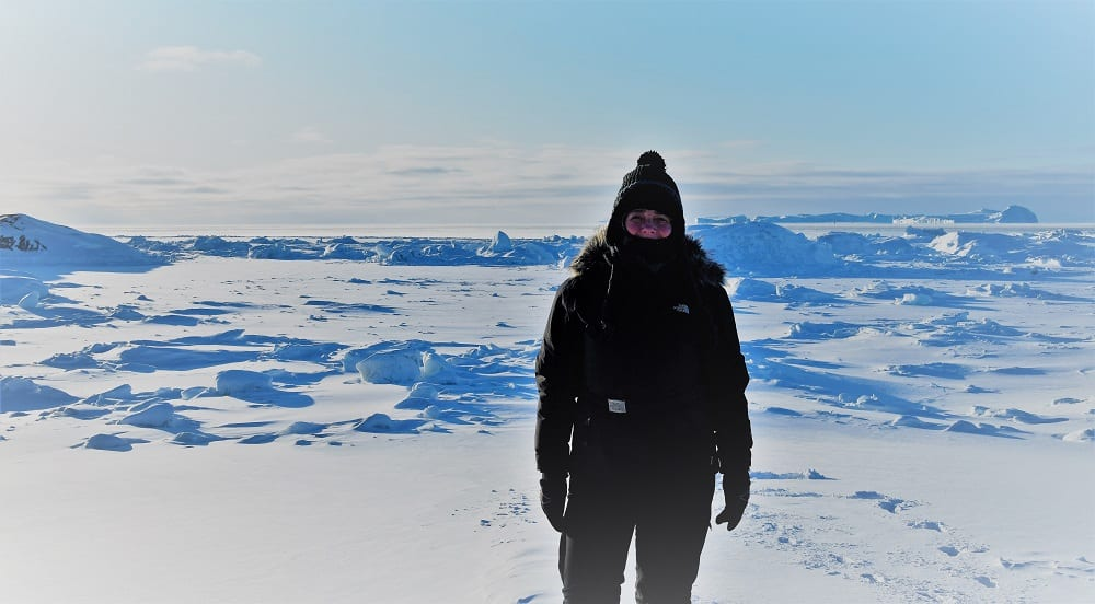 Sue wrapped up in ski gear in front of the ice bound bergs of the Icefjord, Greenland