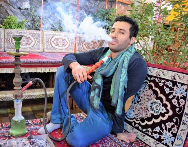 Arash blowing out smoke from the shisha at Darband, Iran