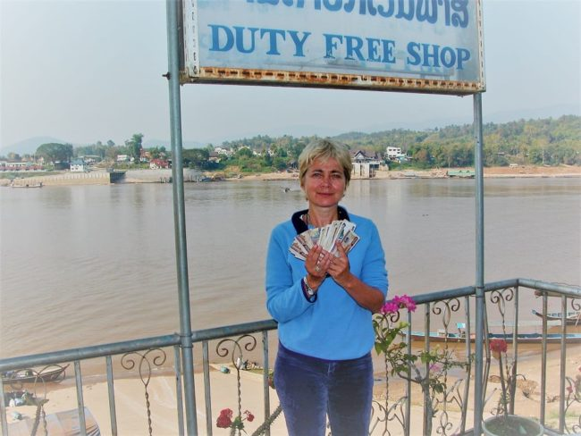 Sue holding Laos currency on a jetty on the Mekong