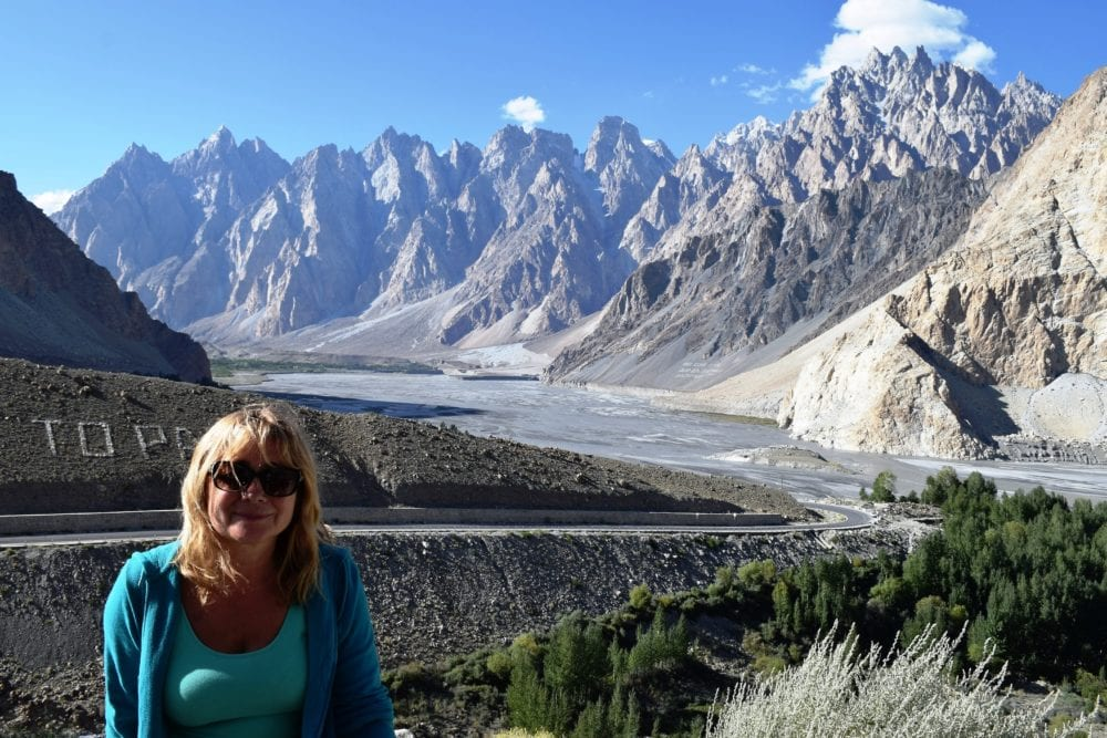 Sue in front of the river and jagged mountain range in the Upper Hunza Valley