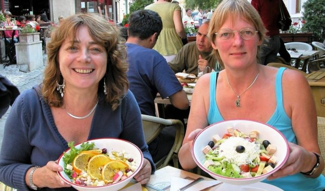 Sue and another tourist displaying our prettily arranged bowls of food at a cafe in Brasov