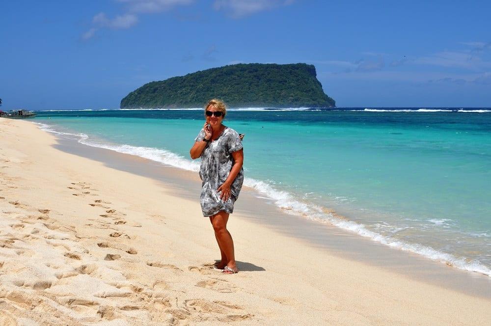 Sue on a beautiful powdery beach in Samoa, a motu behind