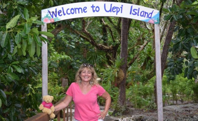 Sue standing under a Welcome to Uepi arch
