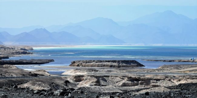 Blue sea, lava flow and volcanic cones framed by mountains