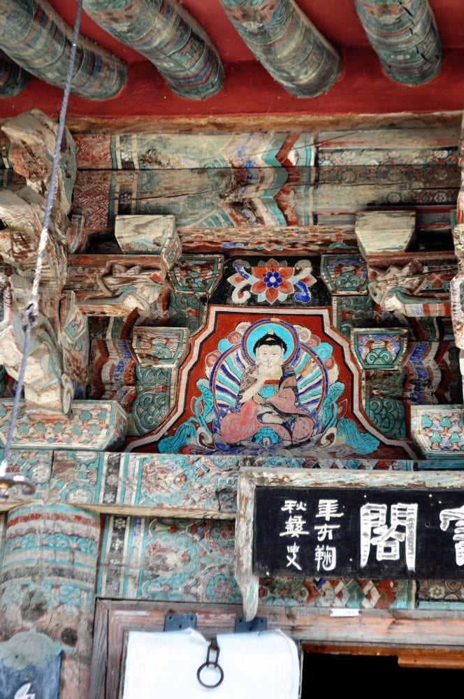 Buddhist decorations on the wall of a building at at the restored village in Gyeongju